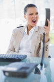 Angry businesswoman screaming at her phone. In bright office Stock Photo