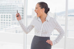 Angry businesswoman screaming at her phone Royalty Free Stock Photography