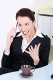 Angry businesswoman screaming to phone. Pretty caucasian businesswoman screaming to phone in the office Stock Photo