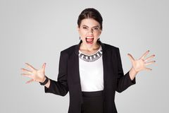 Angry businesswoman shout, roar at camera. Studio shot, indoor. Isolated on grey background Stock Image