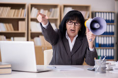 The angry businesswoman shouting with loudspeaker Stock Photo