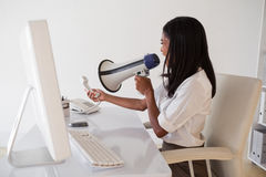Angry businesswoman shouting in megaphone at phone Royalty Free Stock Photography