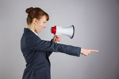 Angry businesswoman shouting through megaphone and pointing Royalty Free Stock Photos