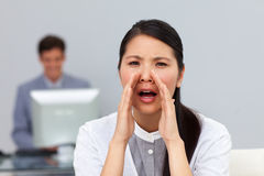 Angry businesswoman shouting in the office Stock Photo