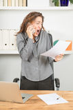 Angry businesswoman shouting on phone with document in hand Stock Image
