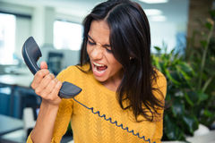 Angry businesswoman shouting on phone. In office Stock Image