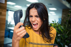 Angry businesswoman shouting on phone. In office Royalty Free Stock Image