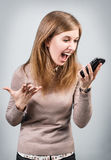 Angry businesswoman shouting on smartphone. Over gray background Royalty Free Stock Photo