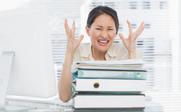 Angry businesswoman shouting with stack of folders at desk Stock Photos