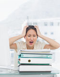 Angry businesswoman shouting with stack of folders at desk Royalty Free Stock Photo