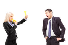 Angry businesswoman showing a yellow card to a businessman shout Stock Image