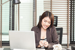 Angry businesswoman sitting with crumpled paper balls at desk royalty free stock photos