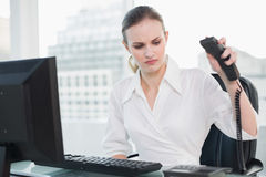 Angry businesswoman sitting at desk hanging up phone Royalty Free Stock Photo