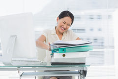 Angry businesswoman with stack of folders at desk Stock Image