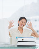 Angry businesswoman with stack of folders at desk Royalty Free Stock Photo