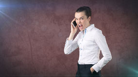 Angry businesswoman, standing by side, talking by mobile phone, emotional screaming, yelling. Isolated studio background Royalty Free Stock Photo