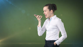 Angry businesswoman, standing by side, talking by mobile phone, emotional screaming, yelling. Isolated studio background Royalty Free Stock Photography