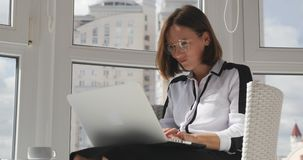 Angry businesswoman in strict clothes and glasses working on laptop  in modern office, quickly typing email, looking at monitor an. Angry businesswoman in strict stock video footage