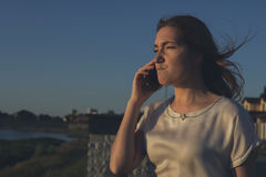 Angry businesswoman talking on phone on the sunset Royalty Free Stock Photos