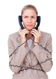 Angry businesswoman tangled up in phone wires Stock Image