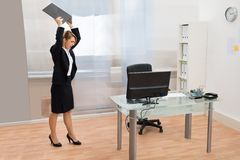 Angry Businesswoman Throwing Laptop. Angry Businesswoman Standing At Desk Throwing Laptop In Office Royalty Free Stock Images