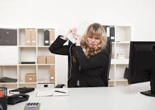 Angry businesswoman throwing a tantrum. Lifting her computer keyboard in the air as though about to strike her desk with it Royalty Free Stock Image
