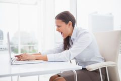 Angry businesswoman using laptop at desk Royalty Free Stock Images