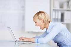 Angry Businesswoman Using Laptop While Screaming At Des Stock Photos