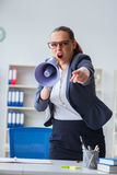 The angry businesswoman yelling with loudspeaker in office Stock Image