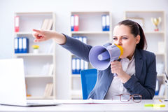 The angry businesswoman yelling with loudspeaker in office Royalty Free Stock Photo