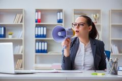 The angry businesswoman yelling with loudspeaker in office Royalty Free Stock Photography