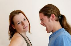 Angry and calm. A shouting, angry young man confronting a woman who is relaxed and unimpressed Stock Image