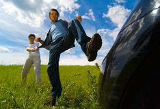 Angry At Car. Young man attempting to kick his car, being held back by another person Royalty Free Stock Photo
