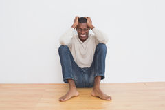 Angry casual Afro man sitting on floor against wall Stock Photography