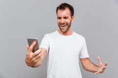 Angry casual man holding smartphone Royalty Free Stock Photo