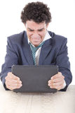 Angry caucasian business male frustrated with work sitting in f. Photo of an angry caucasian business male frustrated with work sitting in front of laptop with Royalty Free Stock Images
