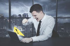Angry caucasian businessman with error message. Angry caucasian businessman getting an error message stock photo