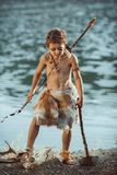 Angry caveman, manly boy with ancient primitive weapon hunting outdoors. Ancient prehistoric warrior. Heroic movie look. Angry caveman, manly boy with stone axe royalty free stock photos