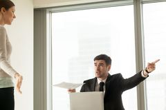 Boss firing woman because of mistakes in report. Angry CEO with report in hand pointing on door, asking to leave responsible for financial mistakes female office Royalty Free Stock Photos