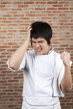 Angry Chef. Asian young chef pose upset, or headache Royalty Free Stock Image