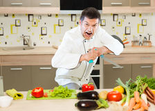 Angry chef cutting vegetables Stock Photography