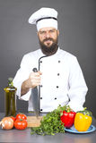 Angry chef with uniform holding a big sharp knife. Over gray background Stock Images
