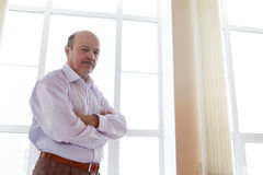 Angry chief glance downwards. Elderly man in white shirt standing at the window in the office Stock Photography