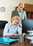Angry chief and secretary in office. Office scene with angry aged chief and elderly female secretary Royalty Free Stock Photo