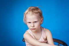 Angry child on a blue background. Angry child looks at the camera on a blue background stock photo