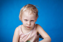 Angry child on a blue background. Angry child looks at the camera on a blue background royalty free stock photos