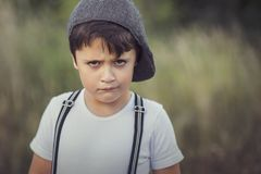 Angry child. Closeup of angry little boy with hat royalty free stock images