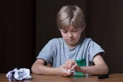 Angry child destroying his drawing. Angry little child at the table destroying his drawing stock images