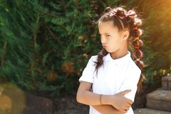 Angry child girl. With pigtails wearing white shirt in a sunny summer park. pine trees on a background stock image