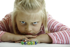 Angry child is lying on the floor. Child (girl) is lying on the floor and looks angry into camera on white background stock image